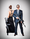 Fashionable couple with automatics women and men holding on gray background Royalty Free Stock Photography