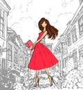 Fashionable cute girl in pink dress walking down the street