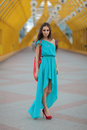 Fashionable girl beautiful smiling in a blue summer dress with red bag Royalty Free Stock Images