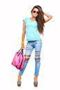 Fashionable girl charming young woman in stylish jeans and sunglasses posing against white background Stock Image