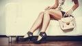 Fashionable girl with handbag sitting on sofa Royalty Free Stock Photo