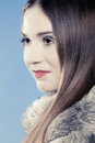 Fashionable girl with long hair in fur coat portrait of young woman on blue studio shot winter fashion Royalty Free Stock Photography