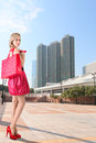 Fashionable girl at shopping young blonde with bags modern cityscape background Stock Image