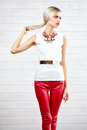 Fashionable girl standing in red leather pants and white top