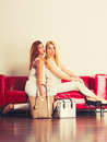 Fashionable girls with bags handbags on red couch Royalty Free Stock Photo