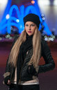 Fashionable lady wearing cap and black jacket outdoor in xmas scenery with blue lights in background portrait of beautiful girl Stock Images