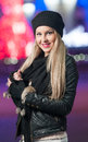 Fashionable lady wearing cap and black jacket outdoor in xmas scenery with blue lights in background portrait of beautiful girl Royalty Free Stock Photos