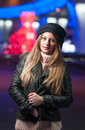 Fashionable lady wearing cap and black jacket outdoor in xmas scenery with blue lights in background portrait of young beautiful Royalty Free Stock Photos
