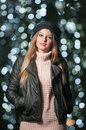 Fashionable lady wearing cap and black jacket outdoor in xmas scenery with blue lights in background portrait of young girl Royalty Free Stock Photo