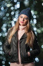 Fashionable lady wearing cap and black jacket outdoor in xmas scenery with blue lights in background portrait of young woman Royalty Free Stock Photography