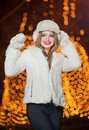 Fashionable lady wearing white fur accessories outdoor with bright xmas lights in background portrait of young beautiful woman Stock Photography