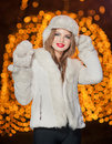 Fashionable lady wearing white fur accessories outdoor with bright Xmas lights in background. Portrait of young beautiful woman Royalty Free Stock Photo