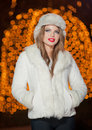 Fashionable lady wearing white fur cap and coat outdoor with bright xmas lights in background portrait of young beautiful woman Royalty Free Stock Photo