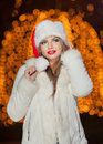 Fashionable lady wearing xmas hat and white fur coat outdoor portrait of young beautiful woman in winter style bright picture Royalty Free Stock Photos