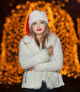 Fashionable lady wearing xmas hat and white fur coat outdoor portrait of young beautiful woman in winter style bright xmas picture Royalty Free Stock Photography