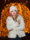 Fashionable lady wearing xmas hat and white fur coat outdoor portrait of young beautiful woman in winter style bright xmas picture Royalty Free Stock Photos