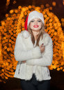 Fashionable lady wearing xmas hat and white fur coat outdoor portrait of young beautiful woman in winter style bright xmas picture Royalty Free Stock Image