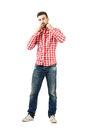 Fashionable man arranging collar on his plaid shirt looking at camera full body length portrait isolated over white background Stock Photos