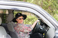 Fashionable mature woman driving car smiling senior wearing black hat sunglasses and lipstick is a Royalty Free Stock Photos