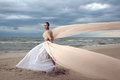 Fashionable model with extremely long dress like a wings vogue style beautiful walks at the beach Royalty Free Stock Photo