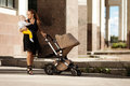 Fashionable modern mother on a city street with a pram young mo trendy walks child in the beautiful women child Stock Photography