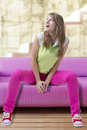 Fashionable teenage style blond woman sitting indoor pink sofa surprised amazed emotion Stock Photos