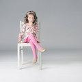 Fashionable thoughtful little girl posing on the white chair looking away long curly hair pink clothes Royalty Free Stock Photography
