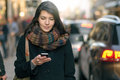 Fashionable woman busy with phone at city street young in black coat and colorful scarf her mobile while walking a Royalty Free Stock Photography