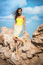 Fashionable woman posing on a beach with rocks in dress Royalty Free Stock Photo