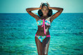 Fashionable woman posing in swimsuit sexy afican american water wearing girl looking at camera summer photo Stock Image