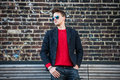 Fashionable young adult stylish man posing outdoors wearing red pulower, jeans, cotton jacket and sunglasses. Royalty Free Stock Photo