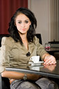 Fashionable young brunette woman having coffee. Royalty Free Stock Photography