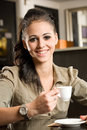 Fashionable young brunette woman having coffee. Royalty Free Stock Photo