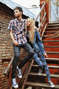 Fashionable young couple standing on stairs and hugging each oth other Royalty Free Stock Image