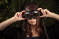 Fashionable young girl in flying helmet on background of tropical leaves Royalty Free Stock Photo