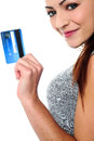Fashionable young girl holding up a credit card cropped image of pretty woman posing sideways with cash in hand Royalty Free Stock Photography
