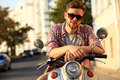 Fashionable young man riding a vintage scooter in street Royalty Free Stock Photo