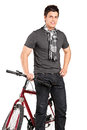 Fashionable young man standing by a bicycle isolated on white background Stock Photos