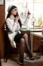 Fashionable young woman in black and white outfit putting lipstick on her lips and drinking coffee in restaurant Royalty Free Stock Photo