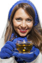Fashionable young woman in a blue knitted winter ensemble and cowl neck jersey sipping cup of hot tea with smile an effort Royalty Free Stock Photo
