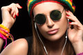 Fashionable young woman enjoying music through headphone feeling the close up wearing rastafarian hat trendy round sunglasses and Royalty Free Stock Images