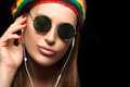 Fashionable young woman enjoying music through headphone feeling the close up wearing rastafarian hat and trendy round sunglasses Stock Photos
