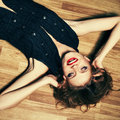 Fashionable young woman lying on wooden floor and laughing Royalty Free Stock Photo