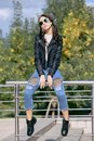 Fashionable young woman in rock style clothes, black leather jacket, blue jeans, tights in a grid under battered jeans Royalty Free Stock Photo
