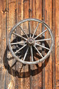 Fassade of an old wooden cottage with cartwheel at sunlight close up Stock Photos