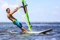Fast approaching windsurfer young man surfing the wind on a bright summer day Stock Image