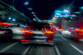 Fast driving traffic at night, blue colors. Abstract blurred background of urban moving car with bright brake lights at Royalty Free Stock Photo