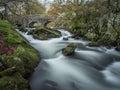 Fast flowing ogwen river passing under bridge and around mossy rocks long exposure snowdonia wales cymru uk Stock Photo