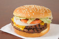 Fast food cheeseburger a double with lettuce pickles tomatoes and a sesame seed bun Royalty Free Stock Photography