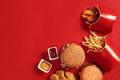 Fast food dish top view. Meat burger, potato chips and nuggets on red background. Takeaway composition. Royalty Free Stock Photo